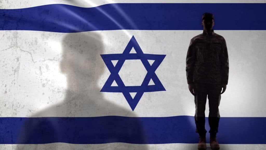 IDF soldier in front of Israeli flag