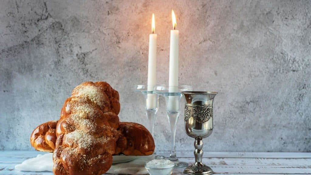 Shabbat table items: Kiddush cup, challot, challah cover, challah board, candlesticks, salt